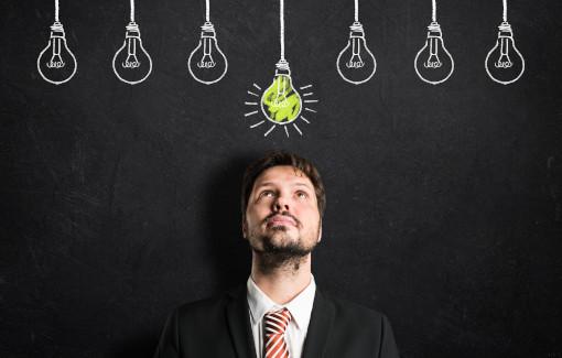 Ein Mann steht vor einer Tafel mit aufgemalten Glühbirnen und schaut noch oben zu einer leuchtenden Glühbirne